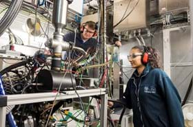 Two students with ear protectors and protective eye glasses look at a big complicated machine