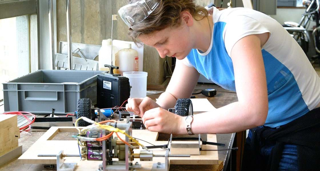 Young student in lab workshop working on electrical engineering project