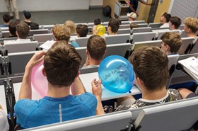 Students in lecture theatre writing questions on balloons