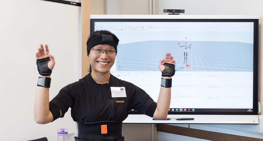 Person wearing motion sensor equipment and smiling