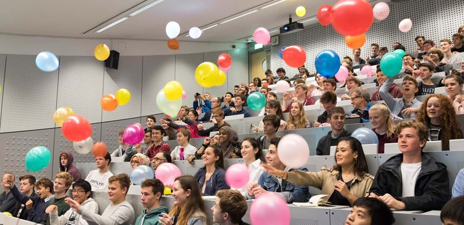 Lecture theatre of people throwing balloons into the air, at open day 2017