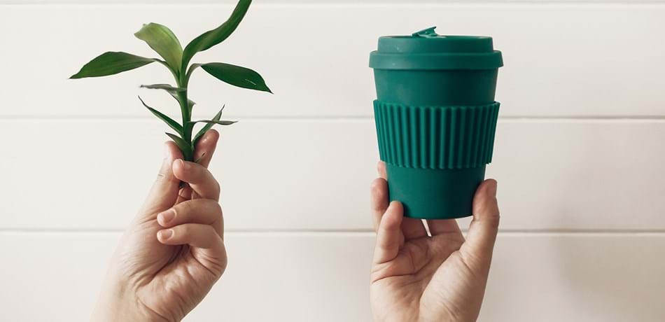Hands holding stylish reusable eco coffee cup and green bamboo leaves on white wooden background