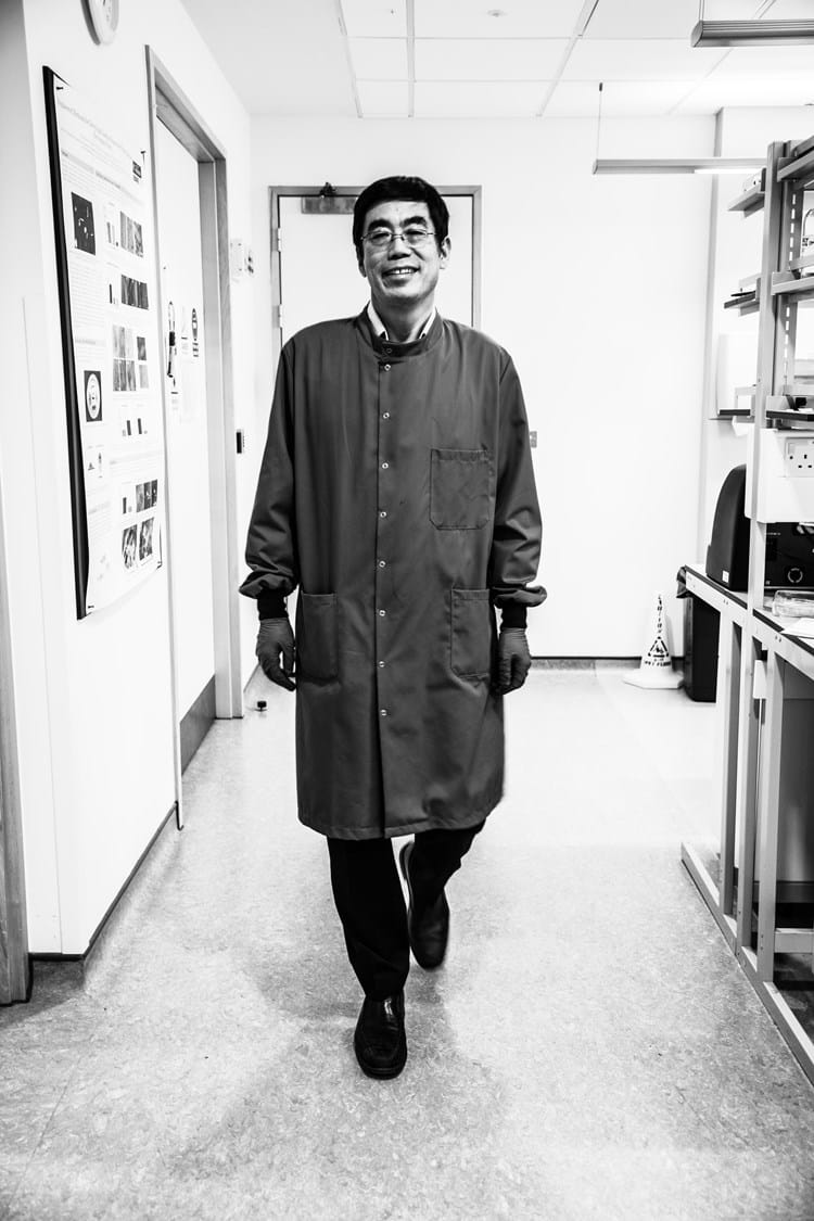 Academic in labcoat smiling and walking