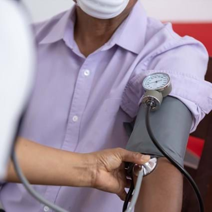 Nurse takes blood pressure of patient wearing mask